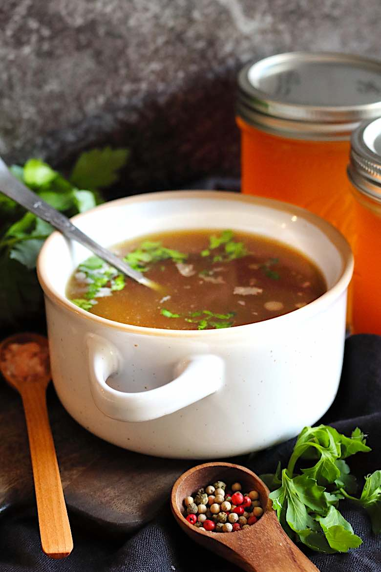 Keto Bone Broth Instant Pot Recipe in a soup bowl with pepperkorn in a wooden spoon