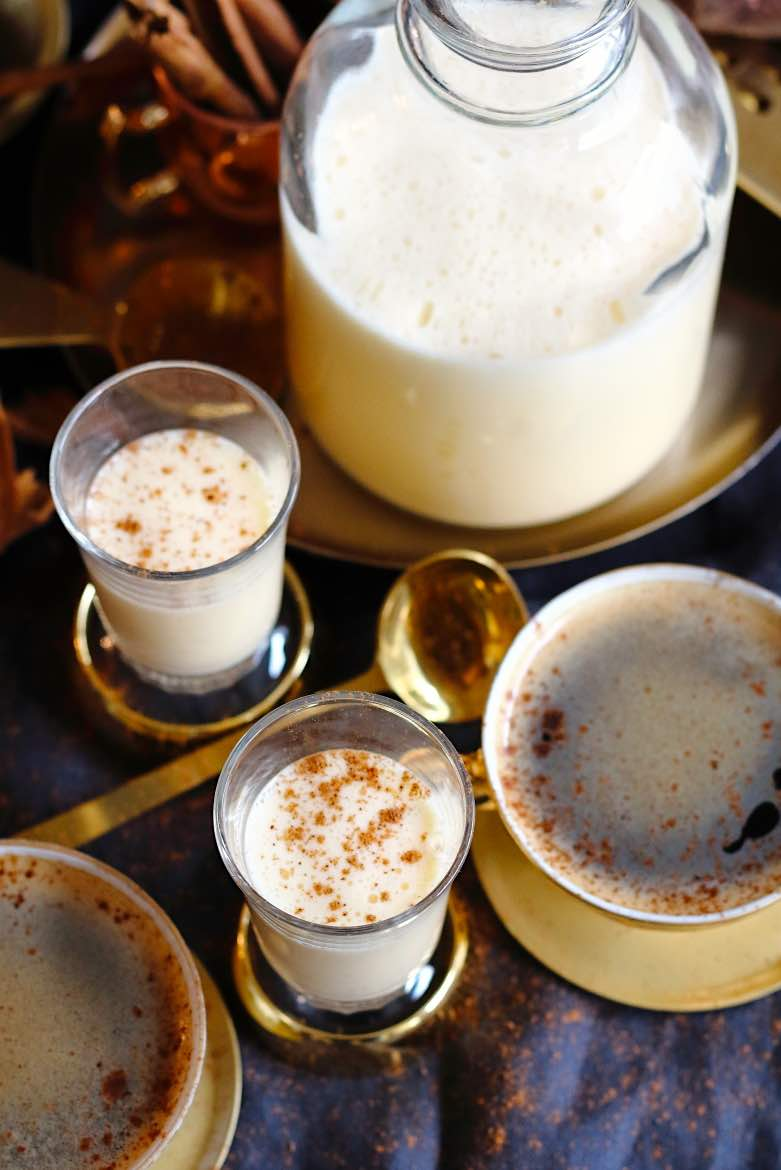 Homemade Almond Milk Keto Eggnog Recipe view from above on bottle and 2 small glasses with golden accessories