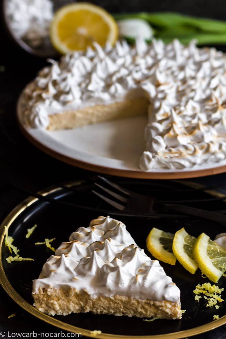 Keto Instant Pot Lemon Cheesecake with Sugar-Free Swiss Meringue Icing cut piece of cake on a black plate