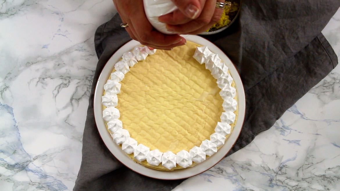 Keto Instant Pot Lemon Cheesecake with Sugar-Free Swiss Meringue Icing step with assemblig and piping the icing on top of the cake