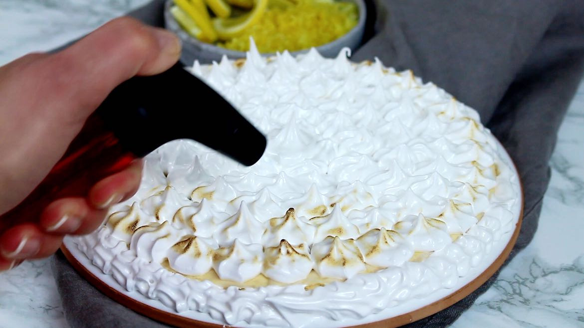 Keto Instant Pot Lemon Cheesecake with Sugar-Free Swiss Meringue Icing step using the torch to brown the icing