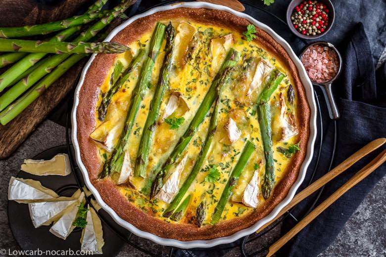 Easy Asparagus Keto Quiche fully baked in white casserole with black background