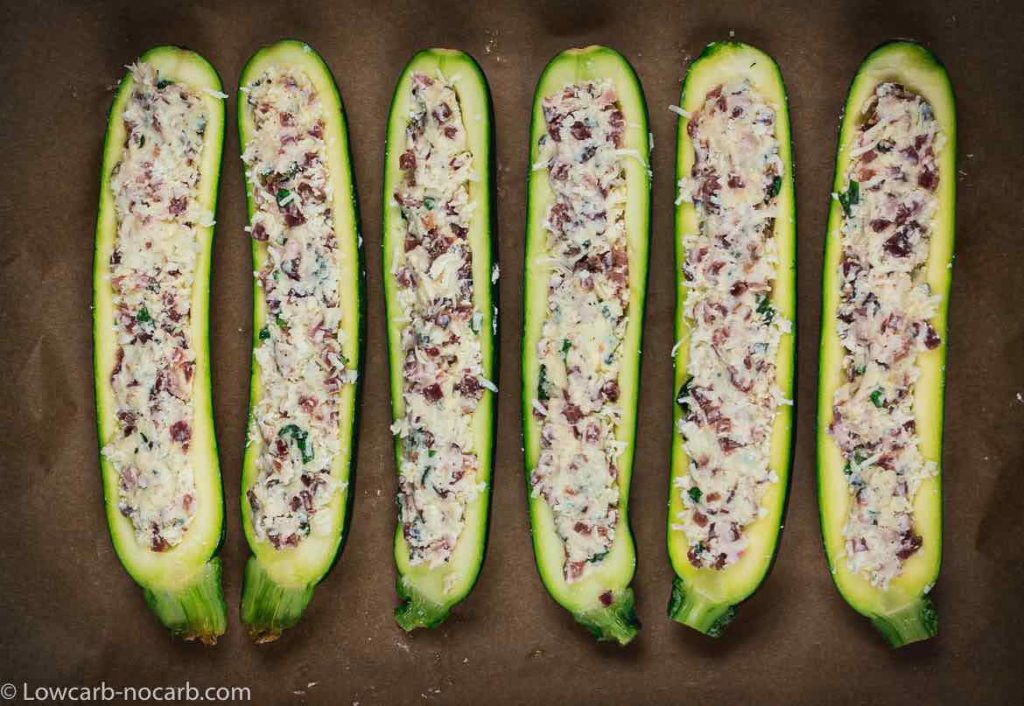 raw Keto Bacon Zucchini Boats filled with cheese mixture