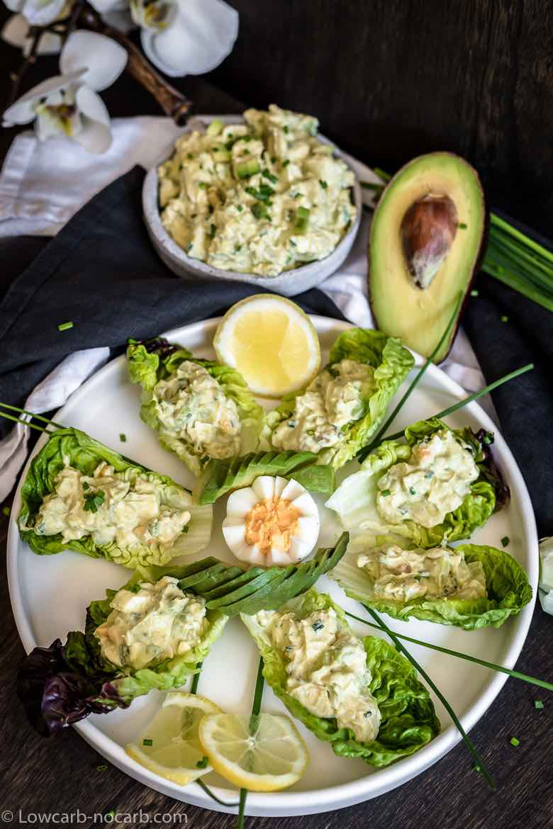 Avocado egg salad decorated on a big white plate