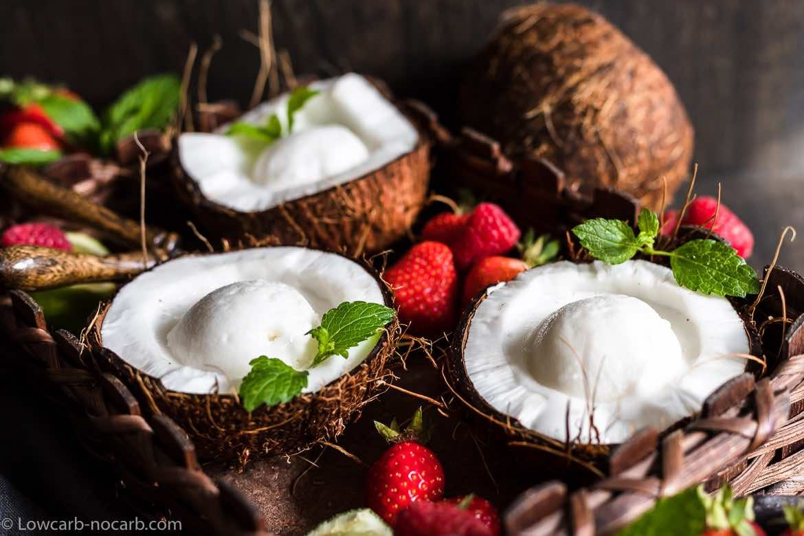 Keto Coconut Ice Cream in 3 coconut bowls surrounded with strawberries