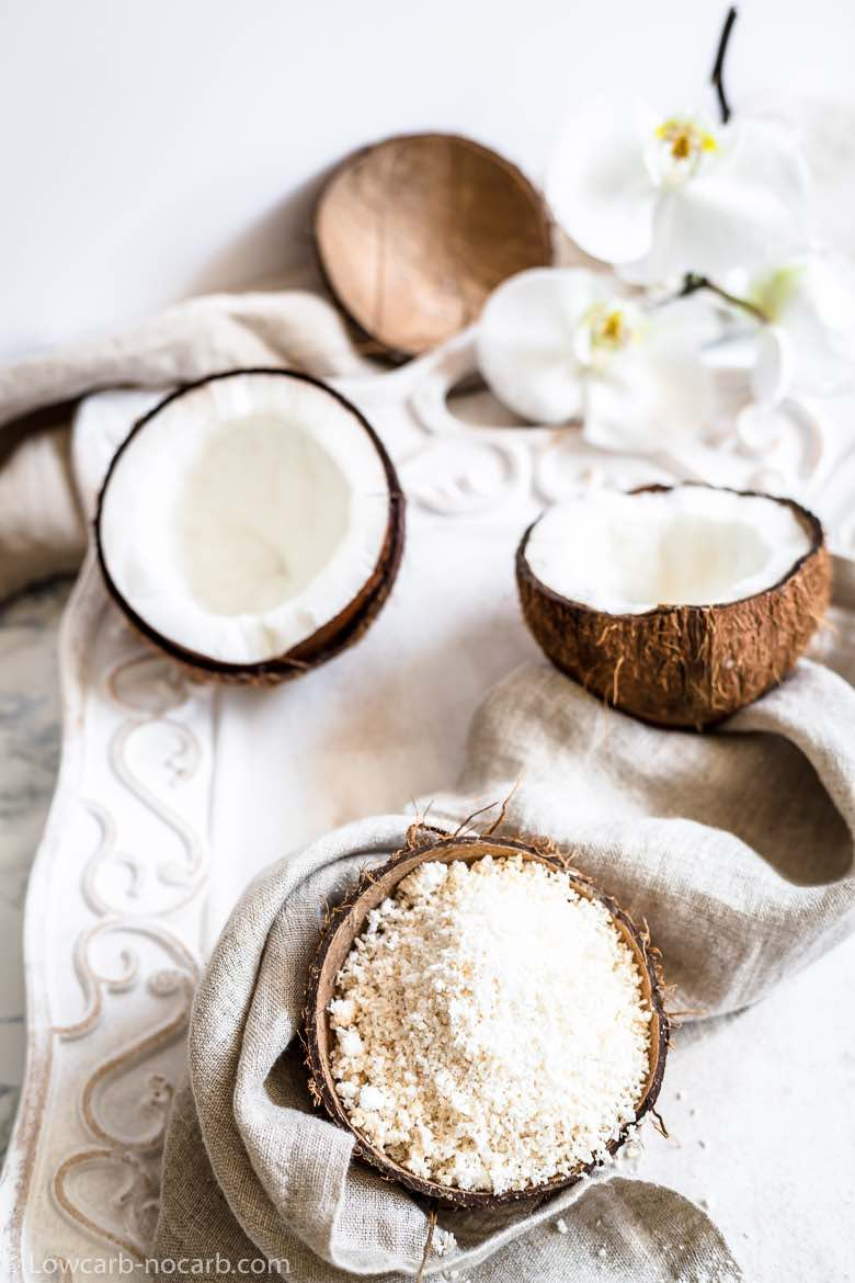 Fresh coconuts with shredded on a white tray with flower in the background
