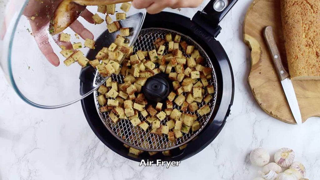 pouring croutons into the Air Fryer