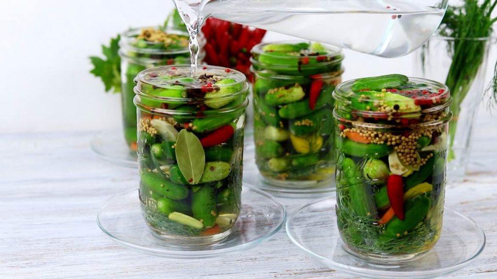 pouring salt brine inside the mason jar for pickles
