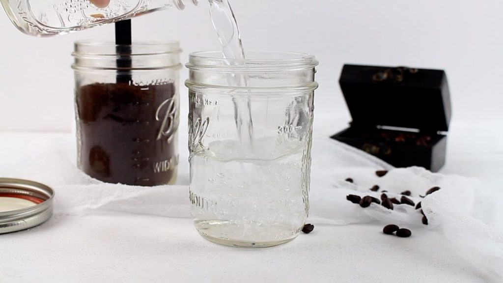 Pouring water into a Mason jar for Cold Brew Coffee making