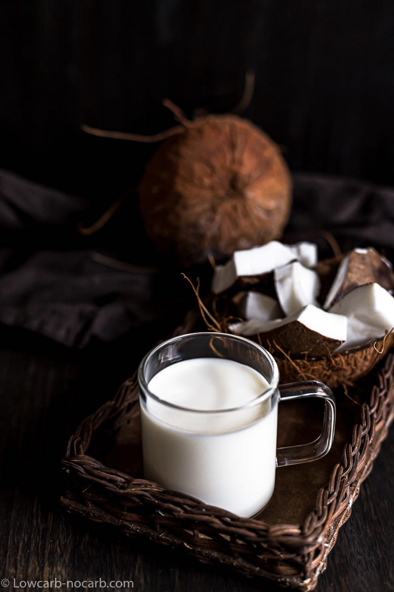coconut milk with whole coconut and pieces of coconut in the background