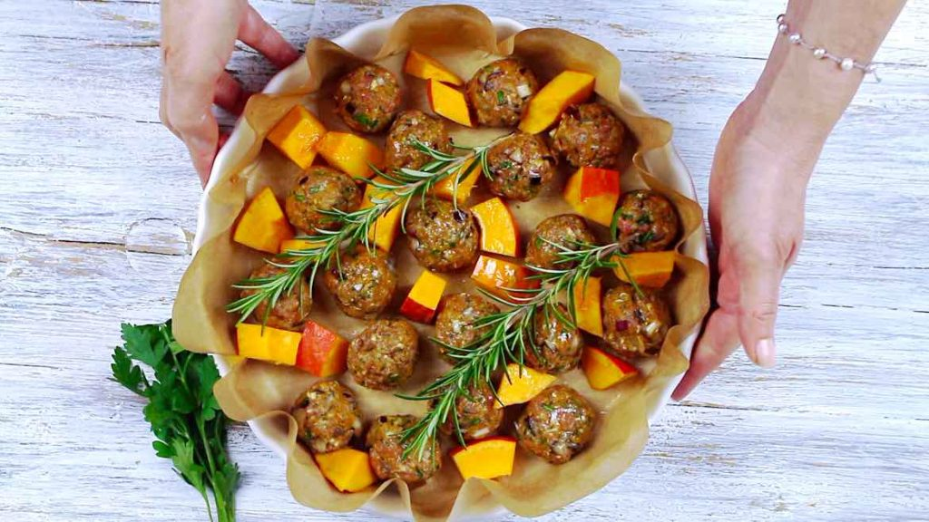 Placing the Keto Meatballs with Pumpkins for roasting