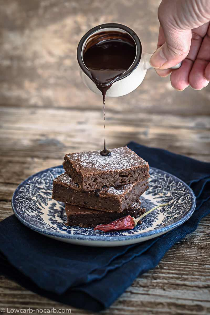 Keto Fudgy Brownies pouring melted chocolate over it
