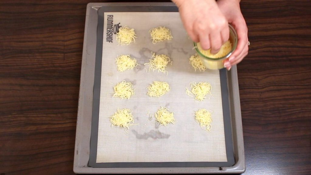 placing grated cheese on a baking sheet