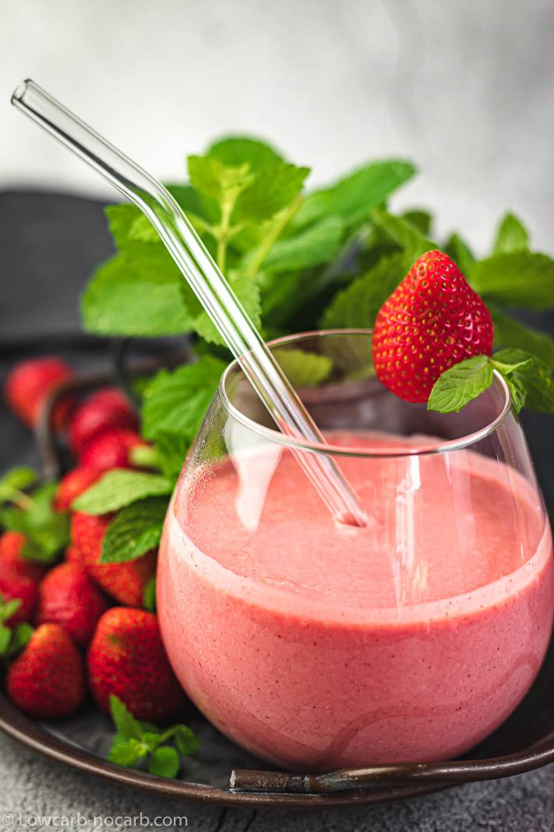 The Best Strawberry Keto Smoothie in a rustic tray with fresh strawberries and mint leaves