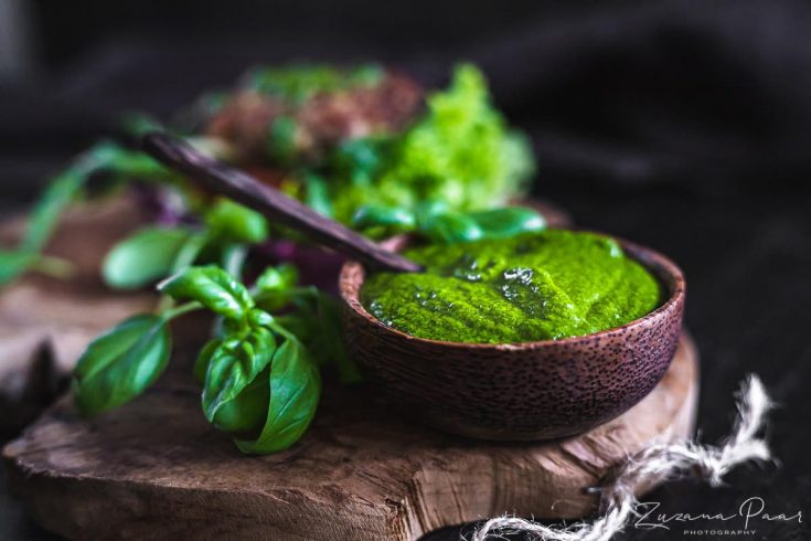 Italian Pesto in a wooden bowl for serving with burger behind