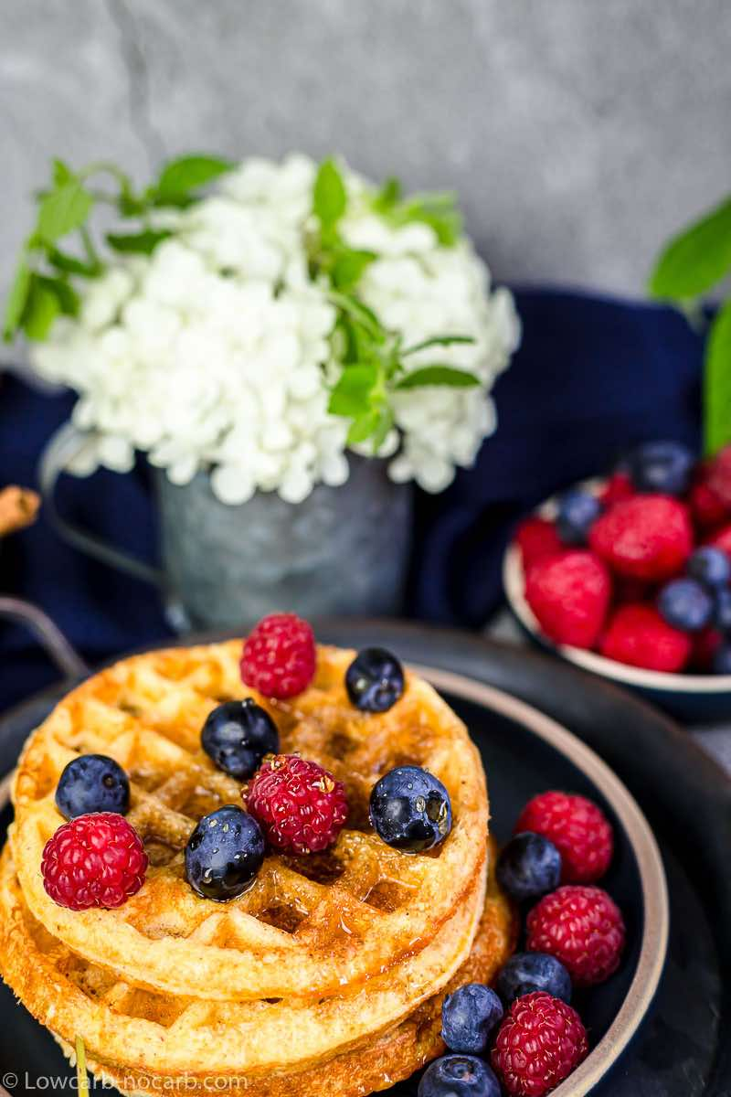 Keto Waffles with berries on a dark plate