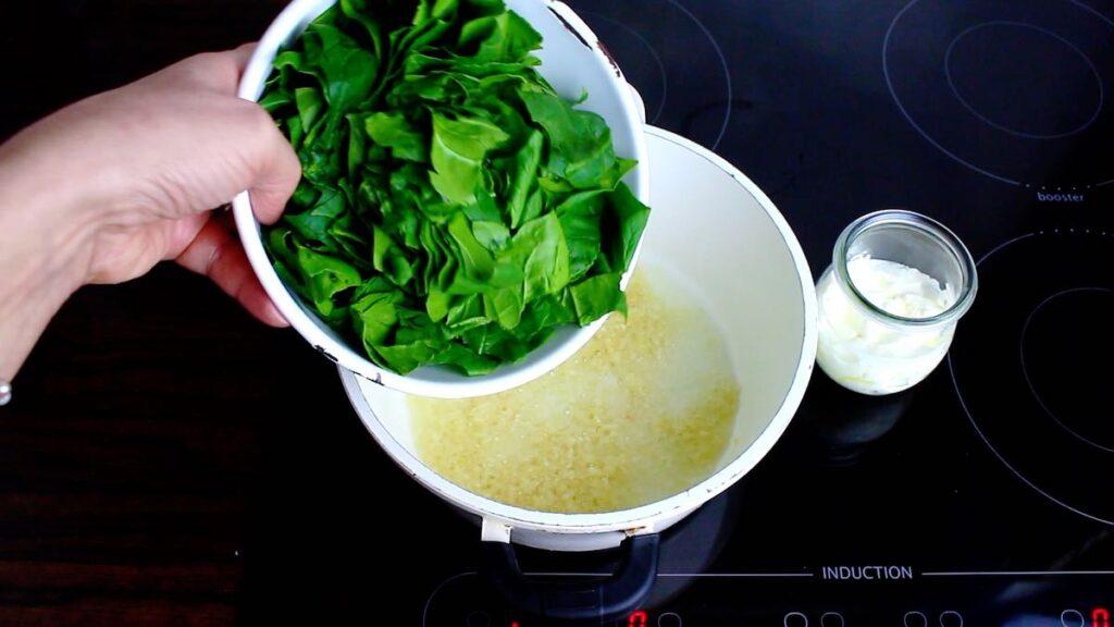Homemade Keto Spinach Gnocchi pouring fresh spinach into the pot