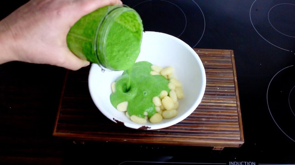 Low Carb Spinach Gnocchi poring spinach sauce