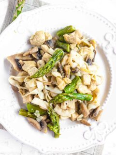 Chiken Noodles mixed with Tofu Shirataki Rice, mushrooms and asparagus on a white plate