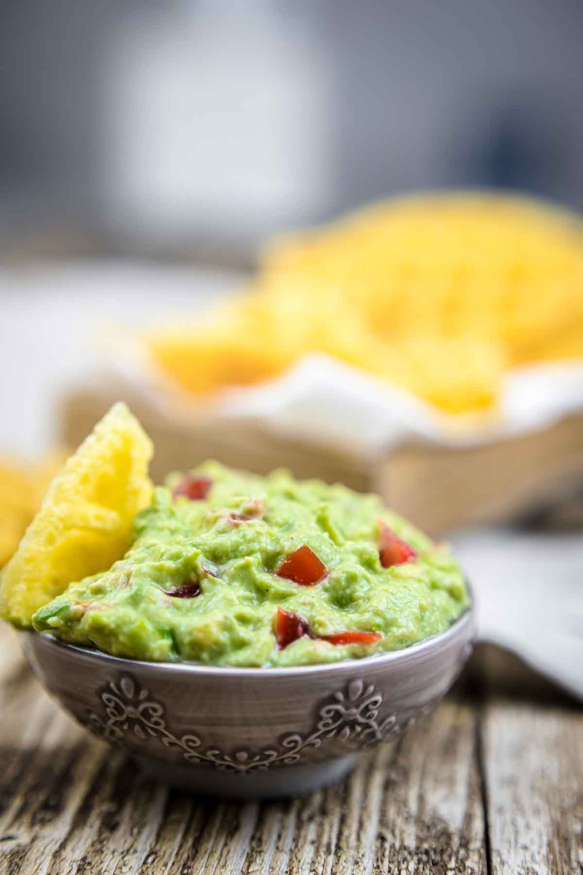 Keto Avocado Dip in a bowl with chips behind