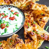 Cheese Bacon Nachos around guacamole bowl