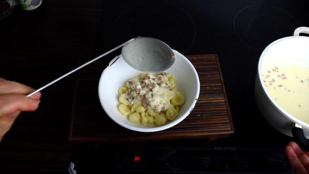 Keto Gnocchi Cream Sauce pouring over the gnocchi