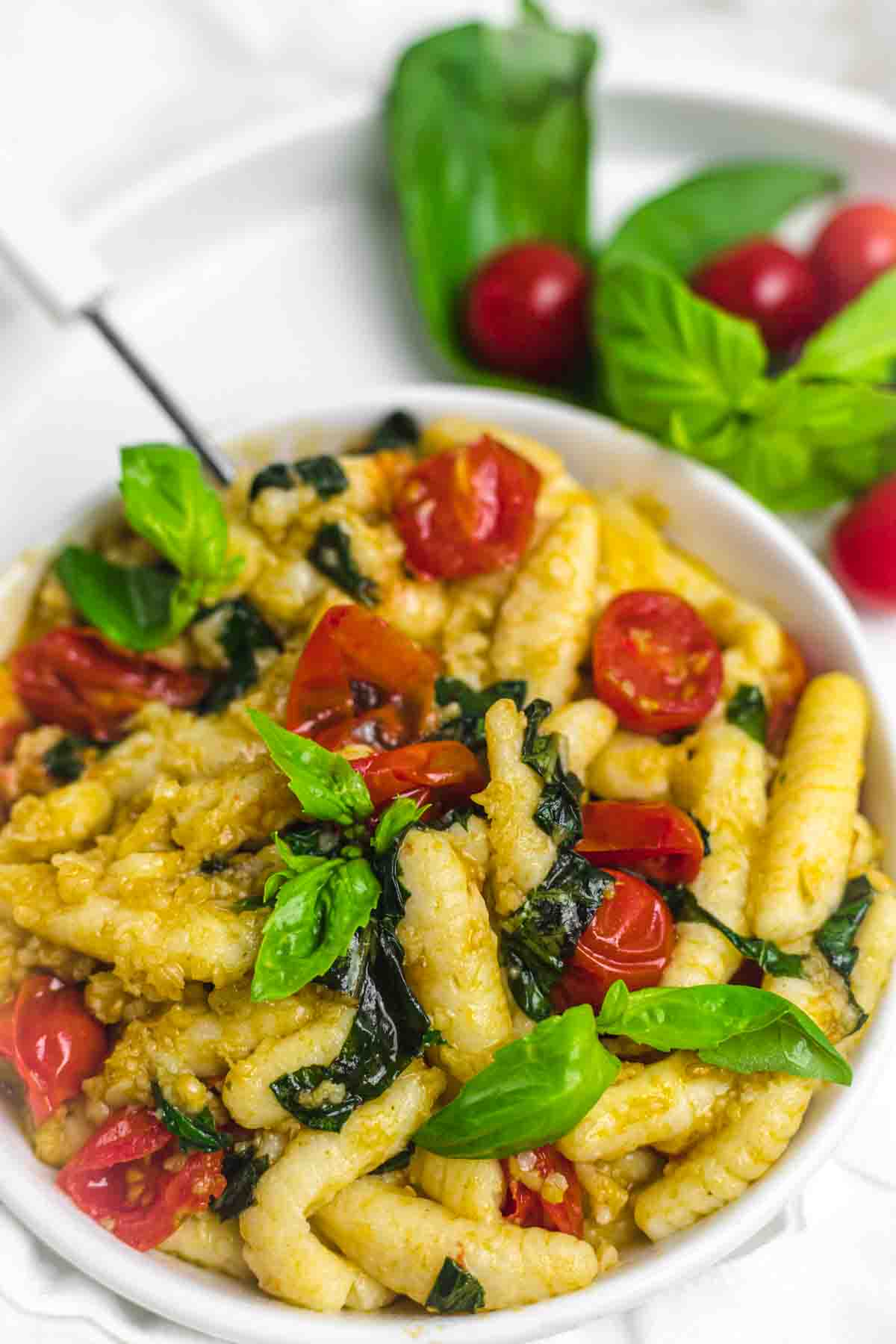 Coconut Flour Gnocchi with tomato and basil on a white plate