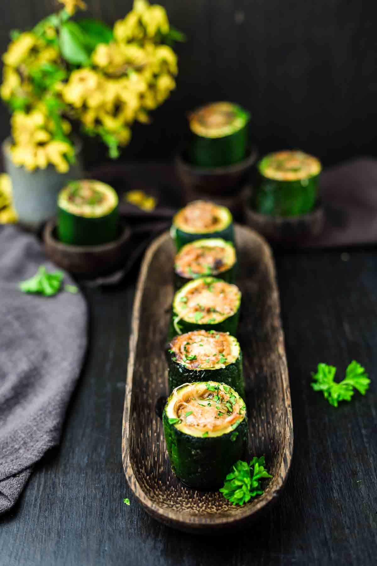 Keto Stuffed Zucchini Mini Bites on a dark wooden board